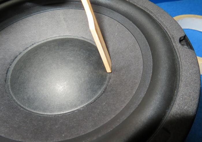 Luidspreker stofkap vervangen - druk met een houten spatel de rand van de stofkap aan